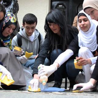 Jugendliche putzen Stolpersteine im Berliner Straßenpflaster