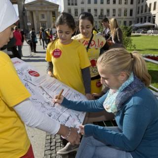 Kinder des Projekts Respektfreunde sprechen mit Passanten und Passantinnen. Hier unterschreibt eine engagierte Bürgerin die Berliner Verpflichtung.
