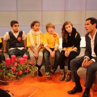 """Mitri Sirin, Moderator ZDF Morgenmagazin, Mitglied im Berliner Ratschlag für Demokratie, im MOMA-Studio mit den Preisträger-Kindern des Projekts """"""""BEIspielhaft""""."""