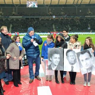Das Gewinnerteam zeigt im Olympiastadion Porträts aus der Ausstellung: Vergessenen Biografien.
