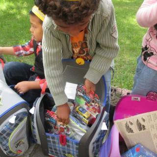 Vier Kinder, die gerade in ihren neuen Schulranzen die Geschenke bestaunen.
